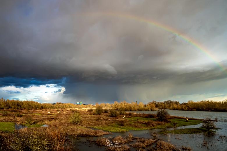 Hagelbui met regenboog - Een flinke hagelbui barst los boven Arnhem. Van een afstandje in de zon zie je vooral de regenboog