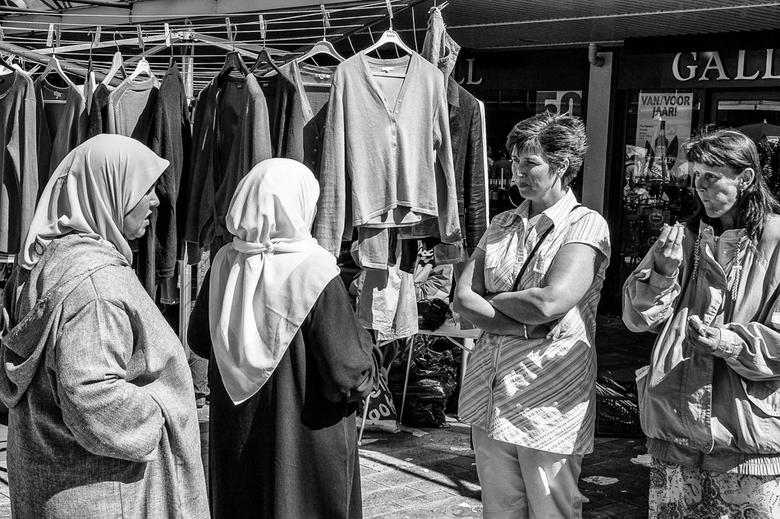 Verschillende Culturen - Soms bekijken culturen elkaar argwanend, zoals hier de twee dames in zomerse kleding enigszins argwanend lijken te kijken naa