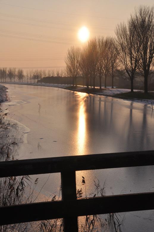 ondergaande winterzon - Met het ijs op de sloot en de ondergaande zon, krijg je altijd zo'n schitterende gloed.