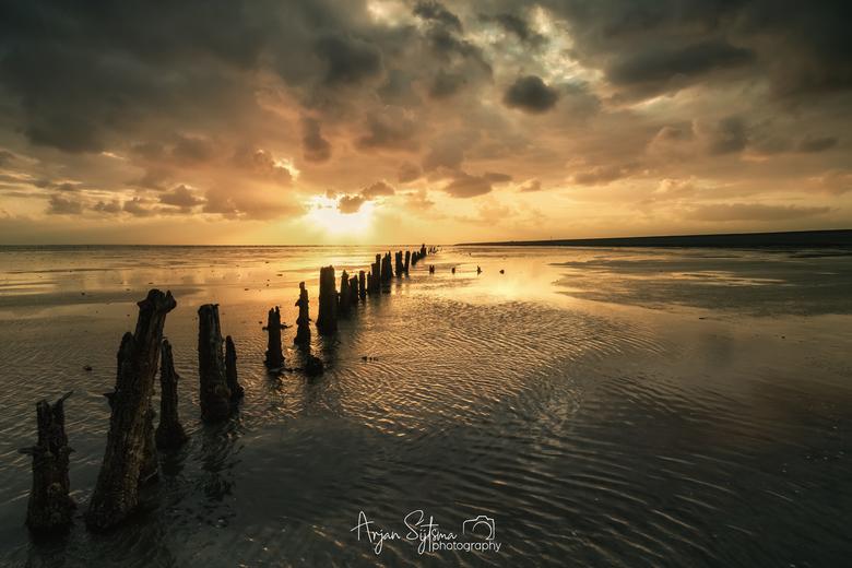 Een regenachtige zonsopkomst op het Wad  -