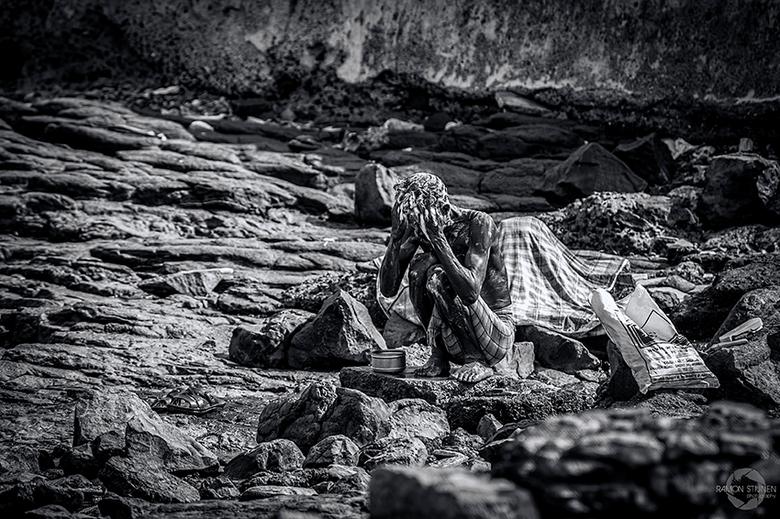 Bath of the poor. - Een man die zich wast op het grillige rotsstrand van Mumbai in India.