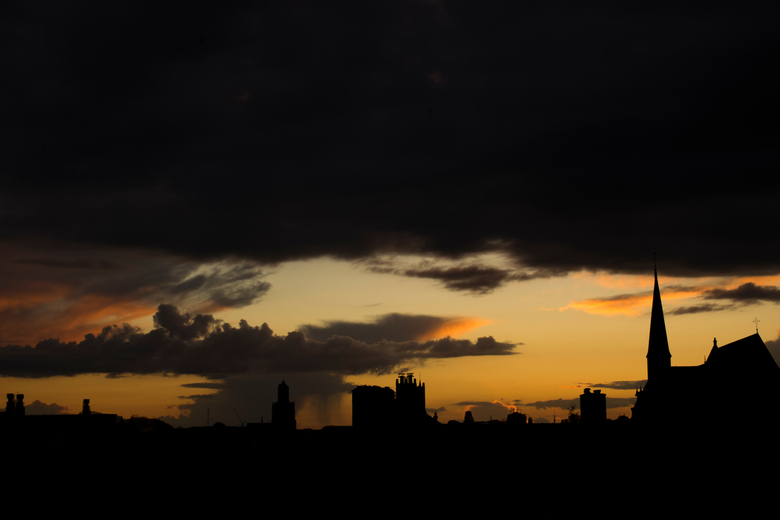 City sunsets  - A rooftop view of the sunset above the city during a cloudy and rainy evening.