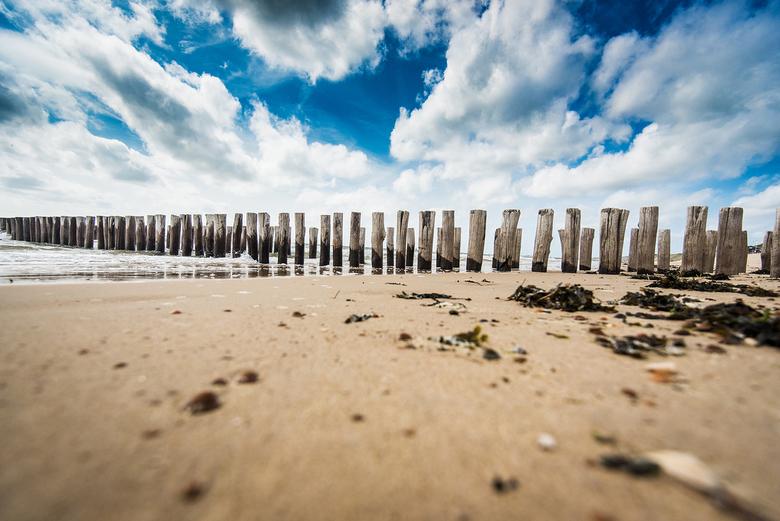 Strand en lucht - Dishoek strand, laag standpunt met paalhoofden