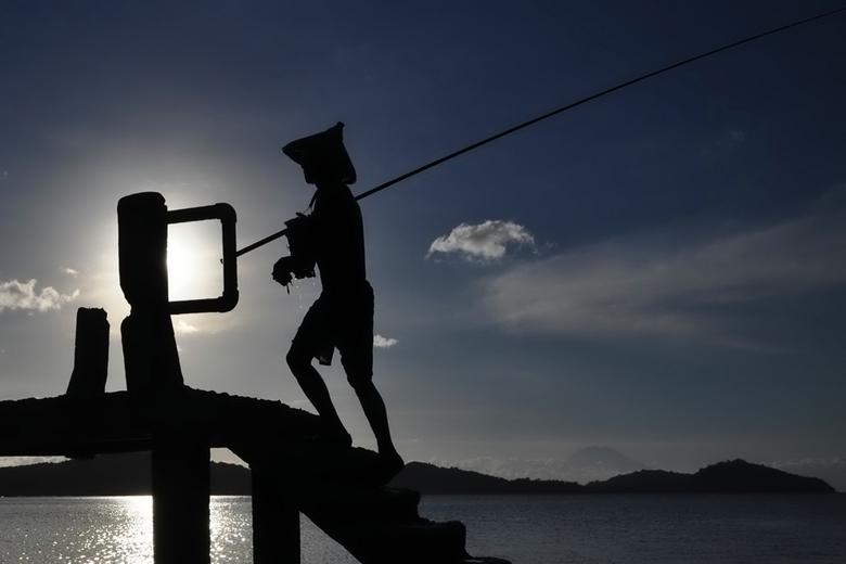 Visser op de pier - Het was op de pier van Pelangan, een klein dorpje op het schiereiland Sekotong op Lombok waar deze visser uit het water kwam om ov