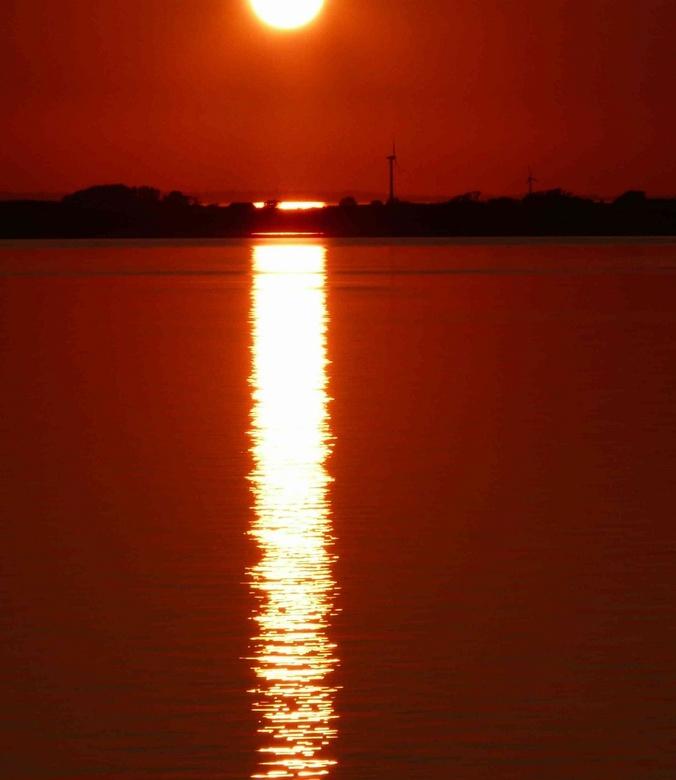 Groene energie gehuld in een rode wereld - Deze foto is gemaakt op de boot van Kiel naar Gotenburg, met uitzicht op Denemarken; het land voor groene e