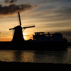 Heimanswetering: boot passeert molen bij ondergaande zon