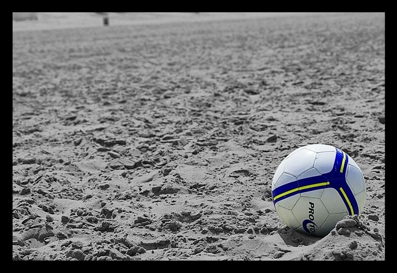 voetbal - een achter gelaten voetbal op een leeg strand