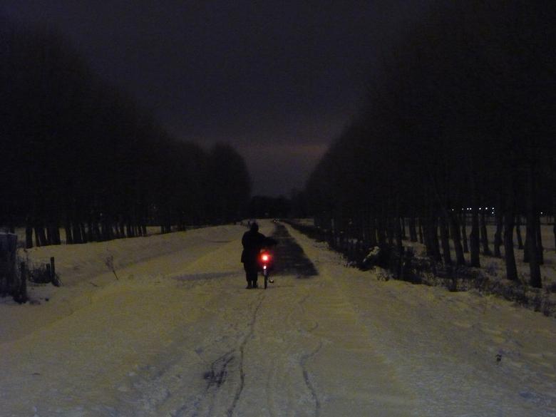 Fietsen in de winter in de nacht - Een vrouw loopt naast haar fiets  door de sneeuw. Vlak voor haar is het fietspad schoongeveegd. Gemeentes voeren el
