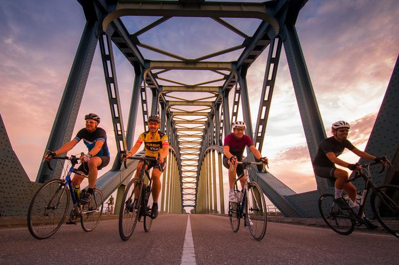 IJsselbrug zonsondergang met wielrenners -