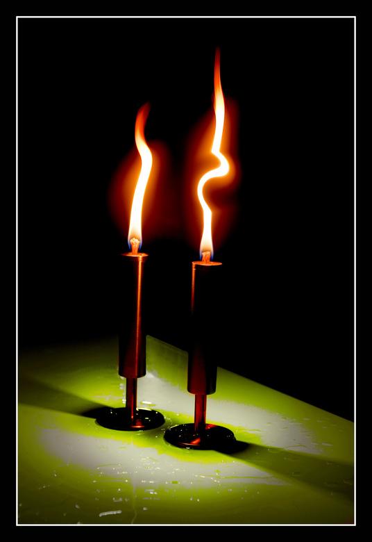 Twee brandende kaarsen. - Bewerkte sfeerfoto van 2 brandende kaarsen op een natte tafel.