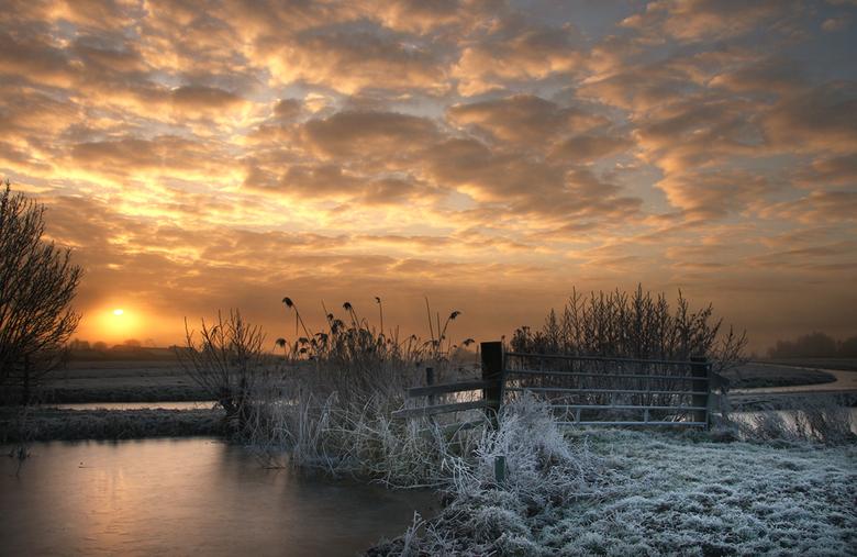 Bevroren hek - een hek in het bevroren landschap terwijl de zon langzaam omhoog gaat.<br /> groeten, bert
