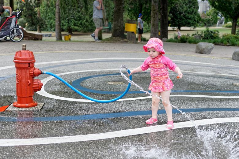 Slingerslang - Een meisje speelt met een waterslang op Granville Island.