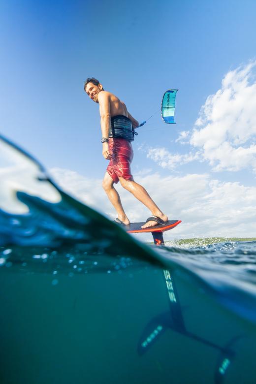 Half om half - Kitesurfer op een foilboard gefotografeerd, half boven water en half onder water waardoor de draagvleugel ook zichtbaar wordt.
