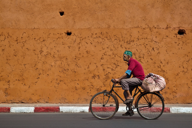 Passing by - De oude stadsmuur van Marrakech en een kleurrijke fietser zorgen voor het decor van deze foto.