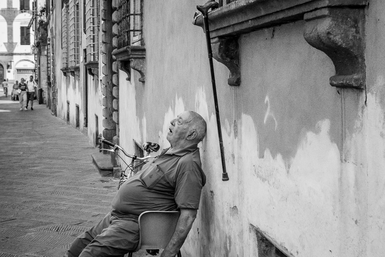 Siesta op straat in Italie - In diepe slaap zat deze man op een stoel in een steegje in Italie. Fiets geparkeerd en zijn stok aan vensterbank gehangen
