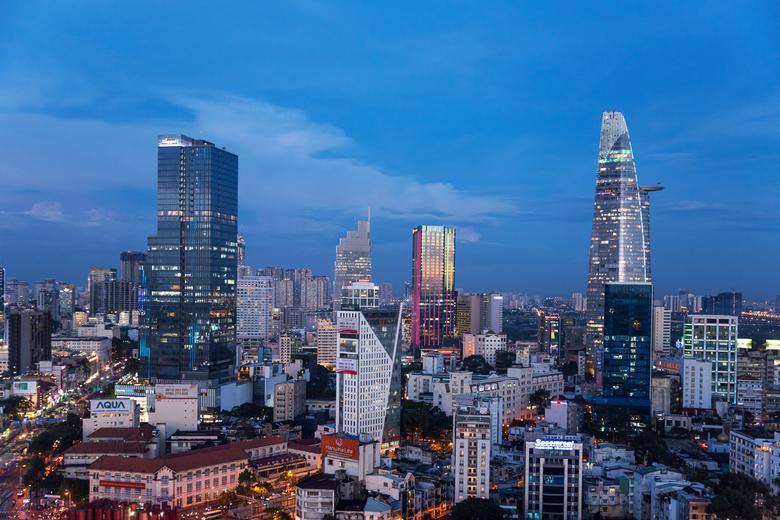 vietnam1750 - Het blauwe uur boven Ho-Chi-Minh stad. De flatgebouwen worden kleurrijk verlicht.