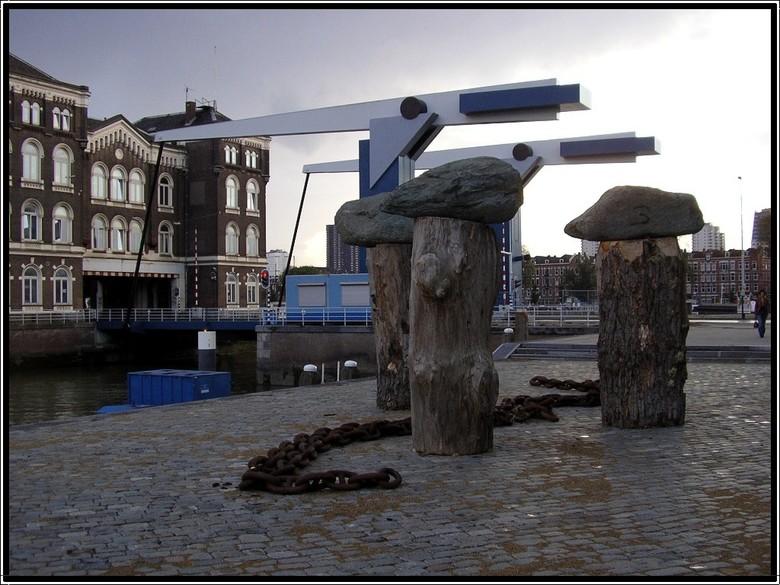 Kunst op Zuid - Oude gebouwen,een brug, en kunstwerken als stukken boomstammen met grote zware stenen erop, en op straat een grote zware ankerketting.