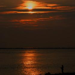 Visser in silhouette met zon's opkomst.
