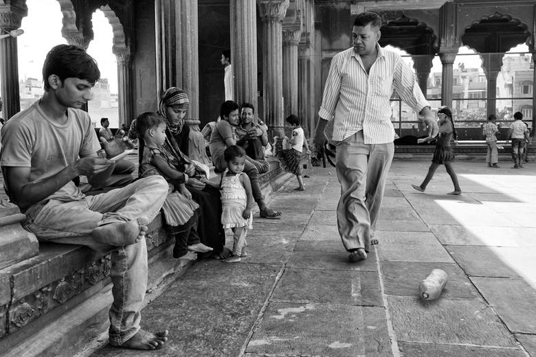 Afkeurend in de moskee - Een man loopt over het binnenplein van de Vrijdagmoskee van Delhi, de grootste moskee van heel India en lijkt afkeurend te ki
