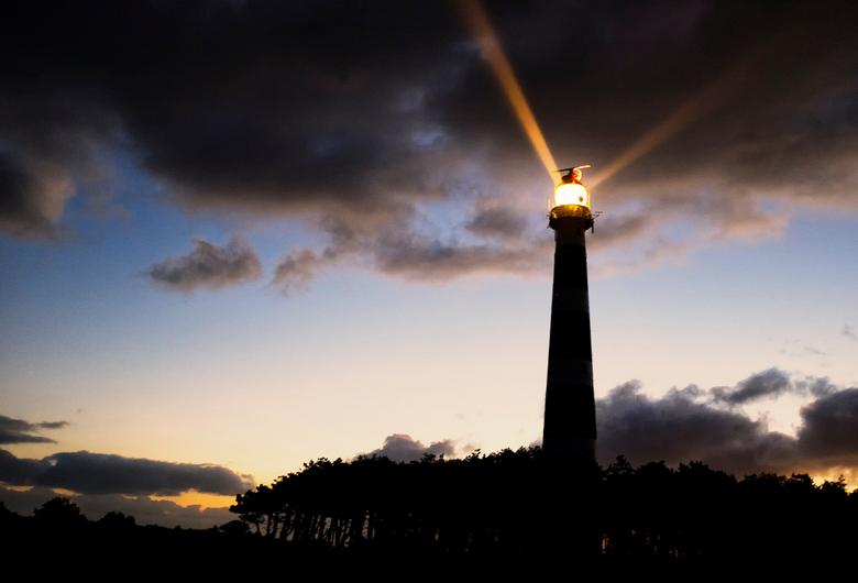 Beam me up - De vuurtoren op Ameland genomen bij dageraad.  De stralen lijken omhoog te schijnen.