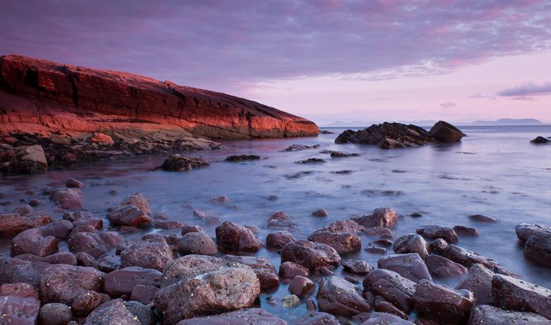 Scottish sunset - Aan de westkust van Schotland, iets ten noorden van Gairloch. Door de ondergaande zon werden de rotsen rood gekleurd.  Door een lang