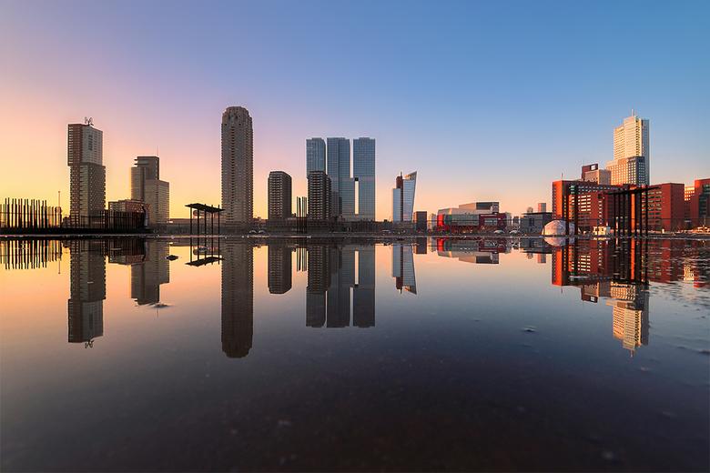 Rotterdam  - De Wilhelminapier in Rotterdam, weerspiegeld in een waterplas op een betonvloer in aanbouw.