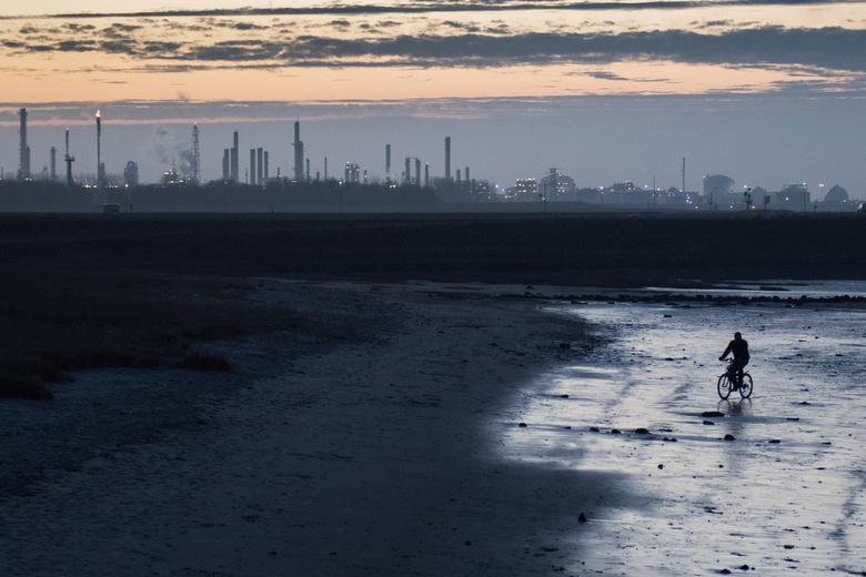 Ons Terneuzen - Met zicht op de industrie tijdens zonsondergang, fietst iemand over het kleine strand
