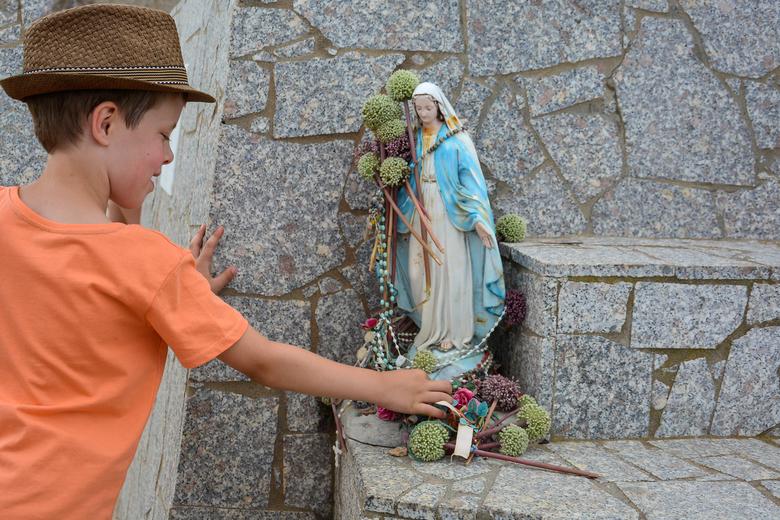 Bloemoffer - Onze zoon zag mensen een bloemoffer brengen bij dit Mariabeeld in Santa Teresa di Gallura (Sardinië) en wilde dat natuurlijk ook!