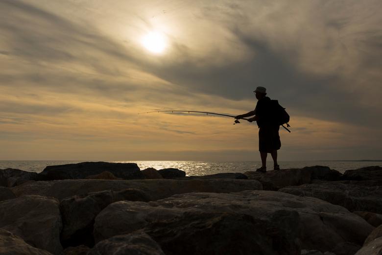 Nog beet voor het donnker?? - Deze visser in het Franse plaatsje Sainte maries de  la mer probeert zijn vangst nog voor het donker binnen te halen.<br