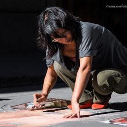 Straatartieste tekent onverstoorbaar in drukke winkelstraat