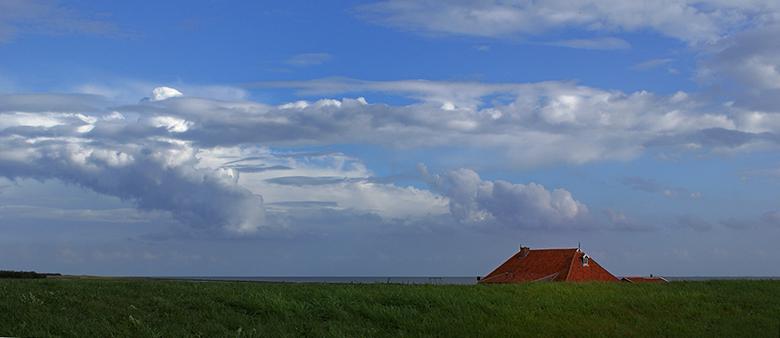 Wierschuur - Het rode dak boven de dijk en dat onder die wolkenlucht.