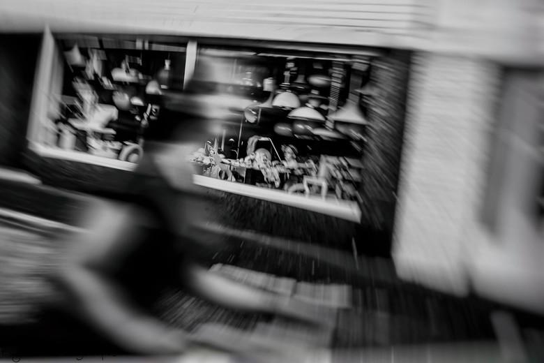 Fiets snel voorbij.... - Straatfoto van snelle fietsen in Almelo, de vintage lampenwinkel op de achtergrond. Met accent op de beweging.