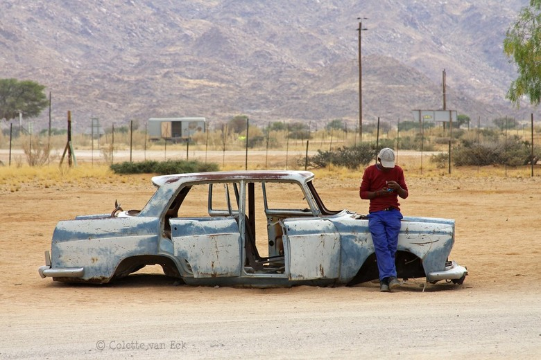Old versus new - Namibia: a man checking his mobile phone while leaning against a old car left there years ago.