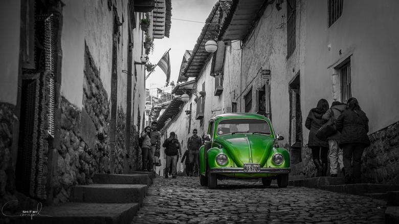 Green beetle - Een groene VW beetle rijdend door de gezellige nauwe straatjes van de San Blas wijk in Cusco.