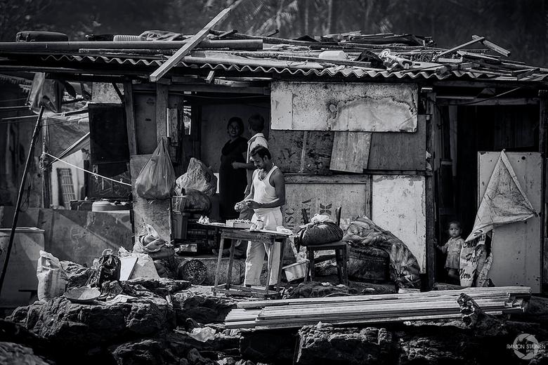 """Sloppenwijk in Mumbai - Een gezin in hun """"woning"""" in een van de velen sloppenwijken Mubai, India."""