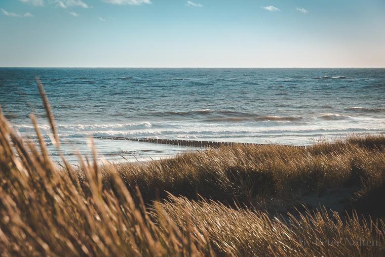 Zon, zee en strand in Zeeland - Een prachtig uitzicht tijdens een ondergaande zon bij Westenschouwen in Zeeland.