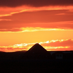 Zonsondergang achter boerderij