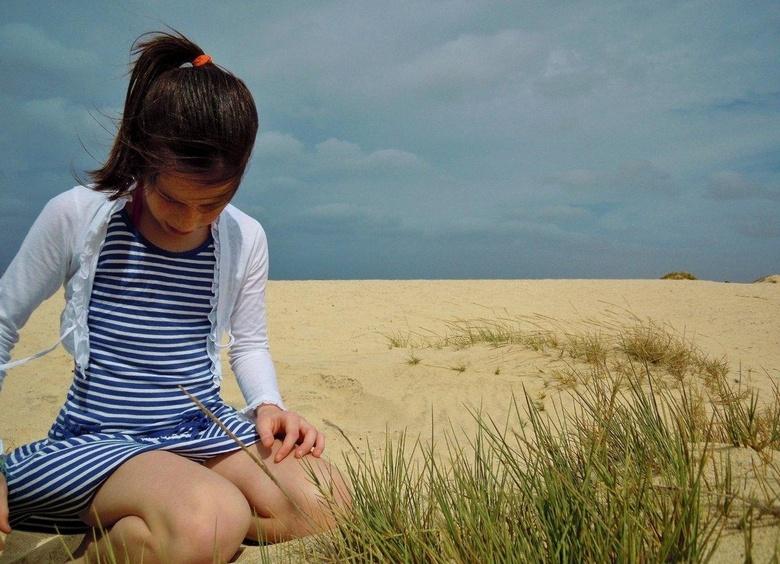 Verlegen - Dit schijnbaar verlegen meisje is mijn dochter (10). Ze nestelde zich op het strand en trok wat van dat stekelgras uit. Een portret zonder