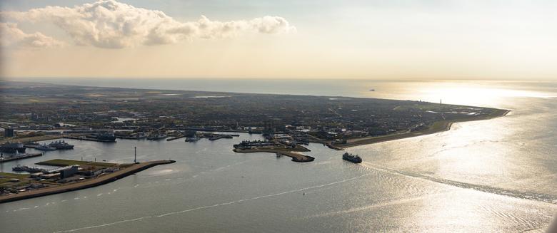 Den Helder - De veerboot van Texel nadert de haven van Den Helder. In het tegenlicht de vuurtoren Lange Jaap die uitkijkt over de Noordzee.