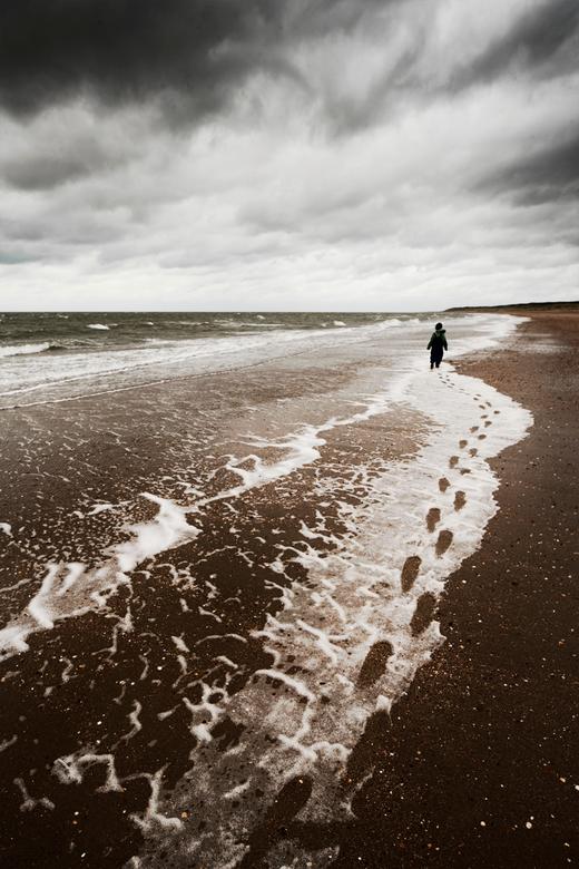 voetstappen - voetstappen in het schuim aan het strand.