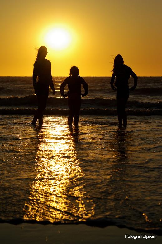 Kinderen spelen tegen-licht - M'n 3 dochters spelend in de zee,
