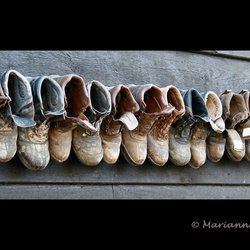 16 schoenen aan een muur.