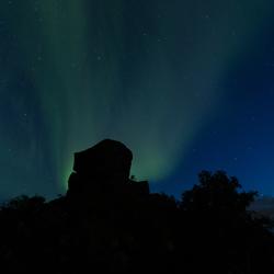 Noorderlicht achter een hoofd op de Lofoten