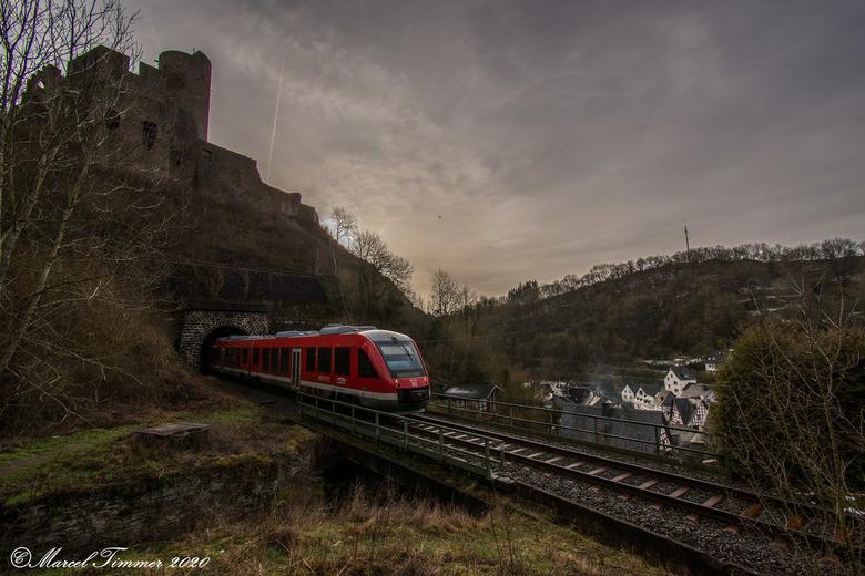 Burgruine Löwenburg Monreal - Een treinstel van DB-Regio, br 648-202, komt bij het opkomen van de ochtendzon uit de Monreal-tunnel, bij het gelijknami