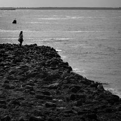 Jonge vrouw op rotsen uitkijkend over zee