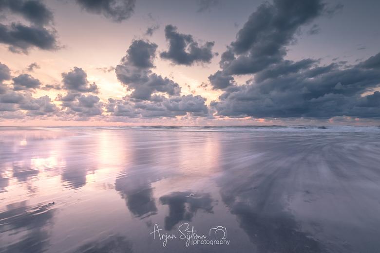 Bewegende spiegel ;) - Er lag een flinterdun laagje water op het strand, waardoor de lucht prachtig gespiegeld werd. <br /> Tevens was het opkomend w