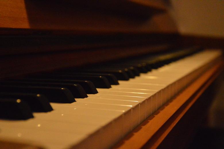 The Piano - Foto met groot scherpteverschil van de piano thuis. Gemaakt in de avond met een geel-oranje lamp. Sluitertijd/ISO/Diafragma weet ik helaas