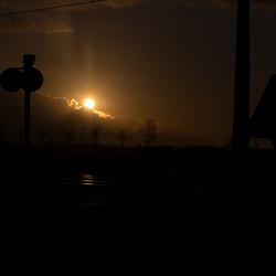 zakkende zon bij spoorwegovergang