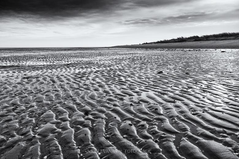 Geribbeld. - Strand Texel, zacht tegenlicht wat door een dunnen wolk scheen. Mooie ribbels en schelpen bij eb.<br /> Omgezet met Nik silver effex pro