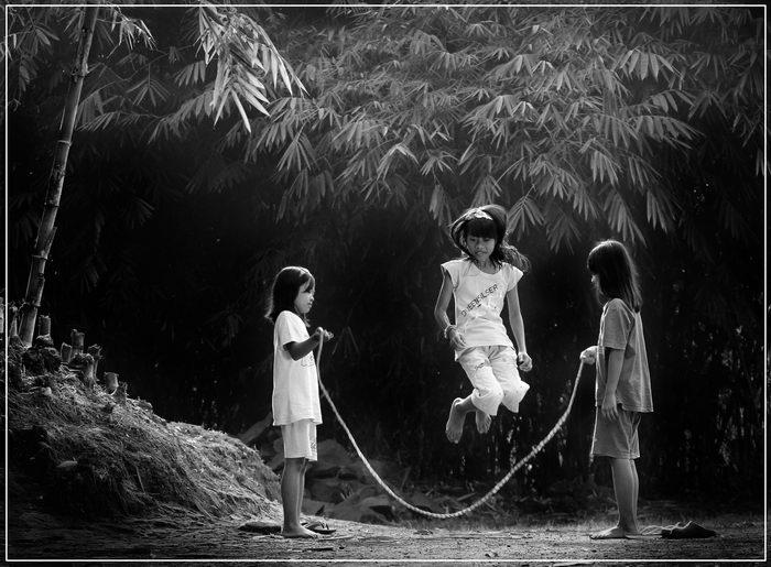 Jump jump - Een paar kleine dorpsmeisjes vermaken zich met een zelf gemaakt springtouw van aan elkaar geknoopte elastiekjes.